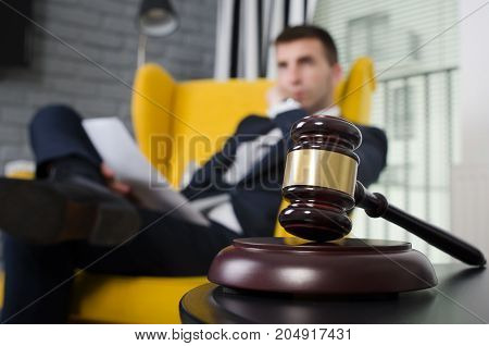 Wooden gavel working lawyer in background. attorney business judgment justice suite analyzing authority background concept