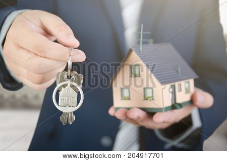Real Estate Agent With Home Keys And House Miniature