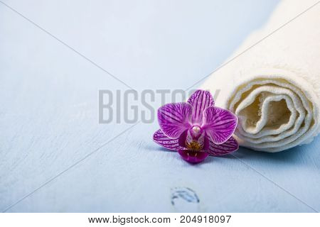 Spa treatments on a blue wooden table. White towel and an orchid flower.