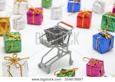 Steel shopping cart and colorful gift boxes on white background. Buying presents concept.