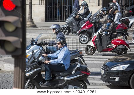 PARIS, FRANCE - June 14, 2013: A few people on scooters are moving through the streets of Paris. Selected focus.