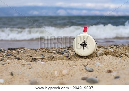 Compass on an enameled mug pointing to the south on the sand of Lake Baikal on the island of Olkhon during the tide of a wave on a mountain background on a summer day.