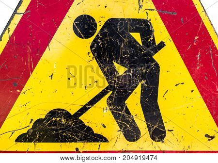 Close-up of men at work sign at a road construction site.