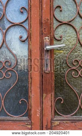 Ancient wooden door with green and blue glass. Made in Italy.