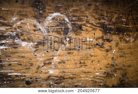 Symbol of heart made with white chalk on a wooden rough panel and rotten.