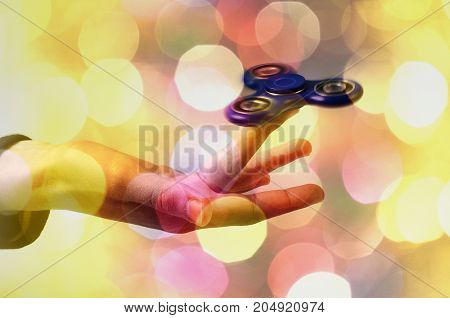 Blue Hand spinner fidgeting hand toy and blur colored spots
