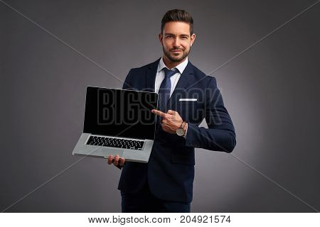 An elegant handsome young man holding and showing the screen of a laptop and pointing on it while looking at the camera
