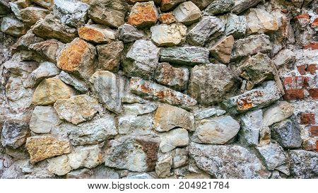 Stone old wall from huge blocks. Background of stones. The concept reliability. The space between the stones is filled with cement.