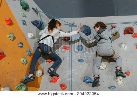 Kids High-fiving On Climbing Wall