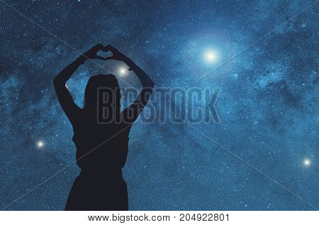 Silhouette of a girl holding a heart-shape.