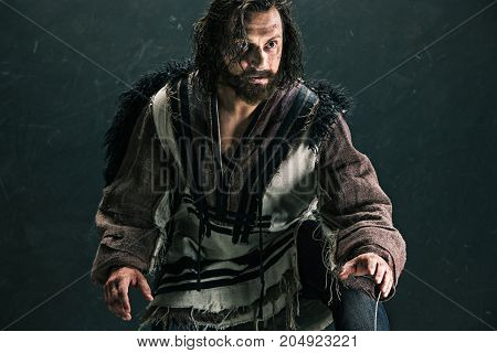 Actor in makeup, a poor man on black studio background. The bum in canvas rags. concept of vagrancy and survival