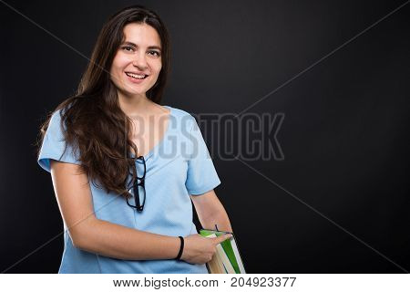 Beautiful Teenage Girl Holding A Pile Of Books