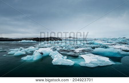 Melting ice on the water in Jokulsarlon lake in south Iceland in cloudy day. Global warming