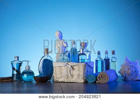 Bath and spa concept. Difeerent cosmetics on glass table and blue background.