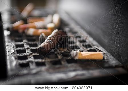 An ashtray full of cigarette butts and a cigar.