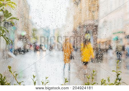 Rain on a window, looking out to people in a street scene, background, selective focus, motion blur