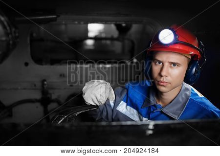 young miner man underground in a mine for coal mining in overalls is busy with work, repairing against the backdrop of mining equipment. Portrait.