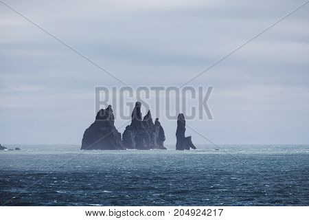 Stone cliff in the ocean in storm cloudy day