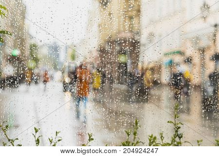 Rainy day in city. People seen through raindrops on glass. Selective focus on the raindrops. Silhouette of girl in bright beautiful coat