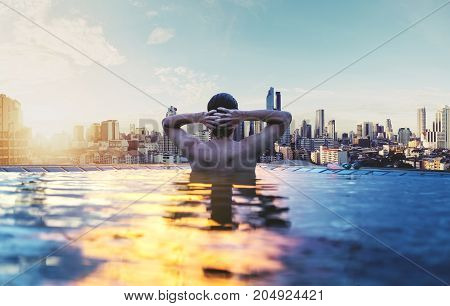 a man relax in swimming pool in sunrise, enjoying city view in the morning