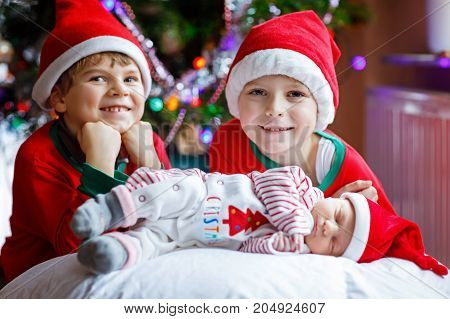 One week old newborn baby girl and two siblings kid boys in Santa hats near Christmas tree with colorful garland lights on background. Closeup of three children, happy family celebrating Xmas