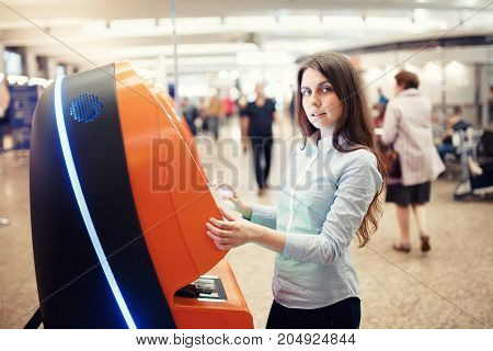 Passenger with Automat for Printing Boarding Tickets in Airport