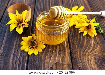 Honey and sunflowers on a wooden background