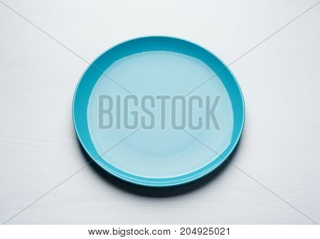 Empty blue plate on white wooden background. Top view with copy space.
