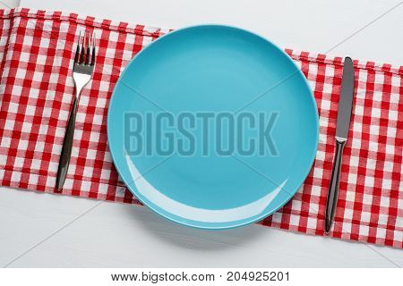 Empty blue plate with cutlery on white wooden background. Top view with copy space.