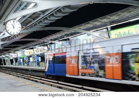 Bangkok Thailand September 10 2017 : Bangkok Sky Train (BTS) in motion at the station stop with the clock on the left of frame mass transit system. (Selective focus on the clock)