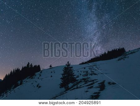 Winter Landscape Of A Mountain Range At Night. Milky Way Over The Mountain Range. Snow Covers Slopes