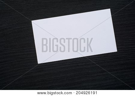 Photo of blank white business cards on a dark wooden background. Mock-up for branding identity .