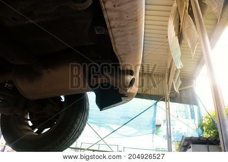 Car undercarriage and exhaust pipe in the garage shop.