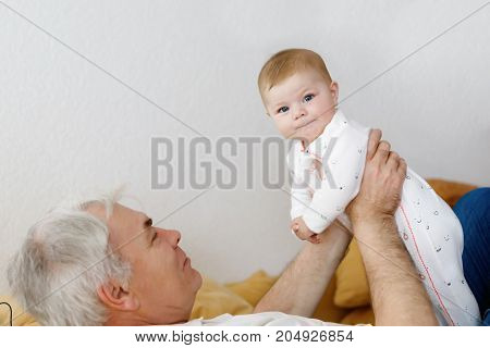 Happy grandfather holding adorable baby girl grandchild on arms. Senior man and cute little girl sitting, playing and laughing together at home. Family, love, grandparents, carefree childhood.