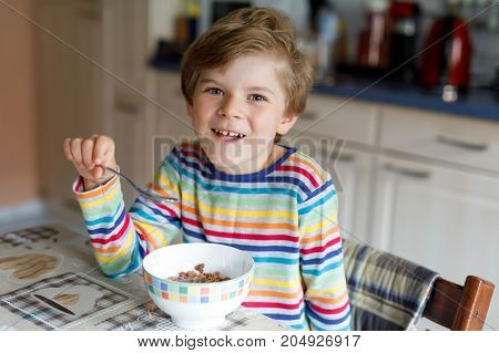 Adorable Happy little blond kid boy eating homemade cereals for breakfast or lunch. Healthy eating for children. At nursery, at school canteen or at home.
