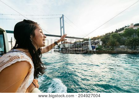 Emotional young girl traveler waving to people on the shore, traveling on a yacht