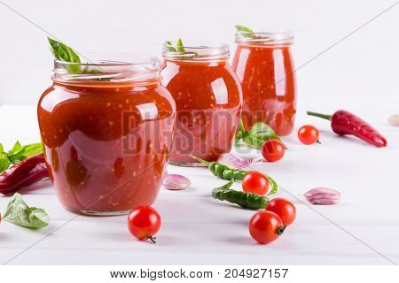 Homemade preserved ketchup in glass jars. On a white background
