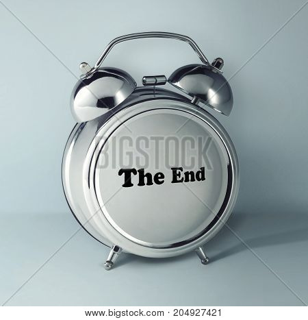 The conceptual image of alarm clock with word THE END on empty clock face against gray studio background. concept of the end of the process