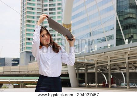 Portrait of attractive business woman raises office document folder to shield from sunlight.