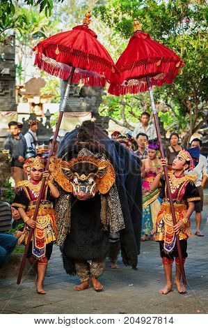 Bali Indonesia - June 21 2015: Dancers in ethnic costumes walk under umbrellas with men in traditional mask of Balinese good spirit Barong on hindu ceremony Ngelawang during temple festival.
