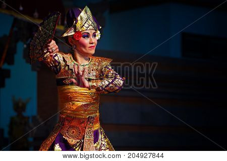 Denpasar Bali island Indonesia - June 28 2015: Face portrait of beautiful Balinese woman in ethnic dancer costume dancing traditional temple dance.
