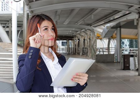 Portrait of young Asian businesswoman have a good idea at outdoor public. Thinking idea business concept.