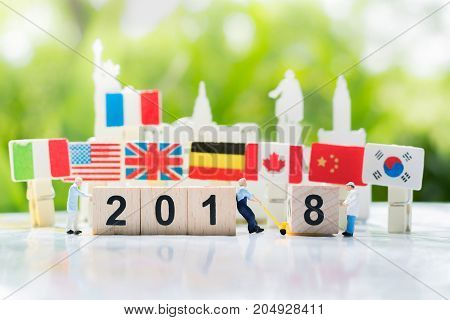 Workers are transferring or pulling a wooden number 8 to link with number 2018 with international flags background using as happy new year 2018 teamwork and partnership business concept.