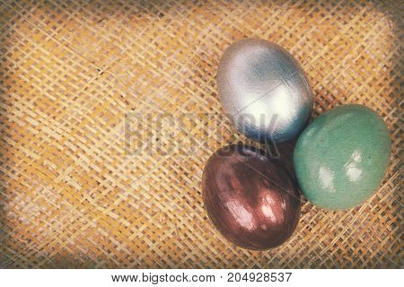 Vintage paper textures Colorful easter eggs on bamboo weave sheet background Easter decoratation with copy space on the left.