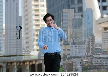 Successful business concept. Double exposure of happy young Asian businessman walking and throwing his necktie in urban building city background.