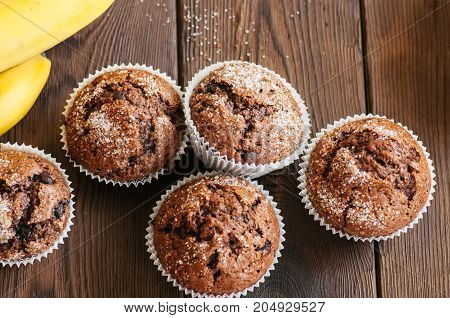 Homemade Banana Chocolate Muffins Sprinkled With Sugar On A Wooden Background.