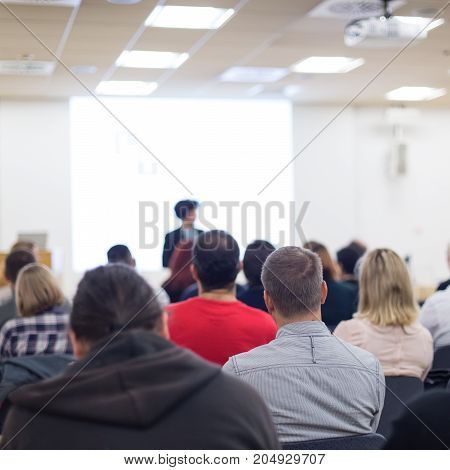 Business and entrepreneurship symposium. Female speaker giving a talk at business meeting. Audience in conference hall. Rear view of unrecognized participant in audience. Copy space on whitescreen.