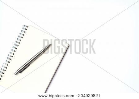 Top view of modern white office desk table with white notebook and pen with copy space flat lay.