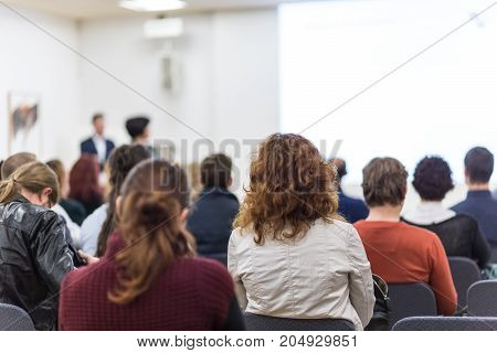 Business and entrepreneurship symposium. Speaker giving a talk at business meeting. Audience in conference hall. Rear view of unrecognized participant in audience. Copy space on whitescreen.