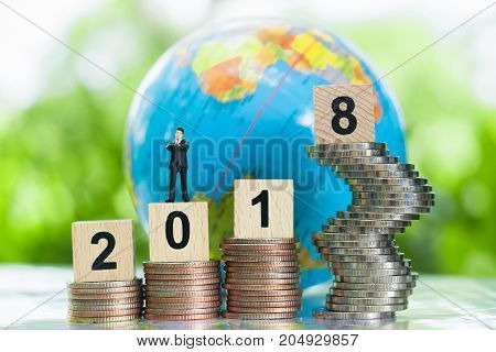 Tiny miniature businessman model is standing on a wooden numbers 2018 on growing stacks of coins with globe background using as growing business and achievement background concept.